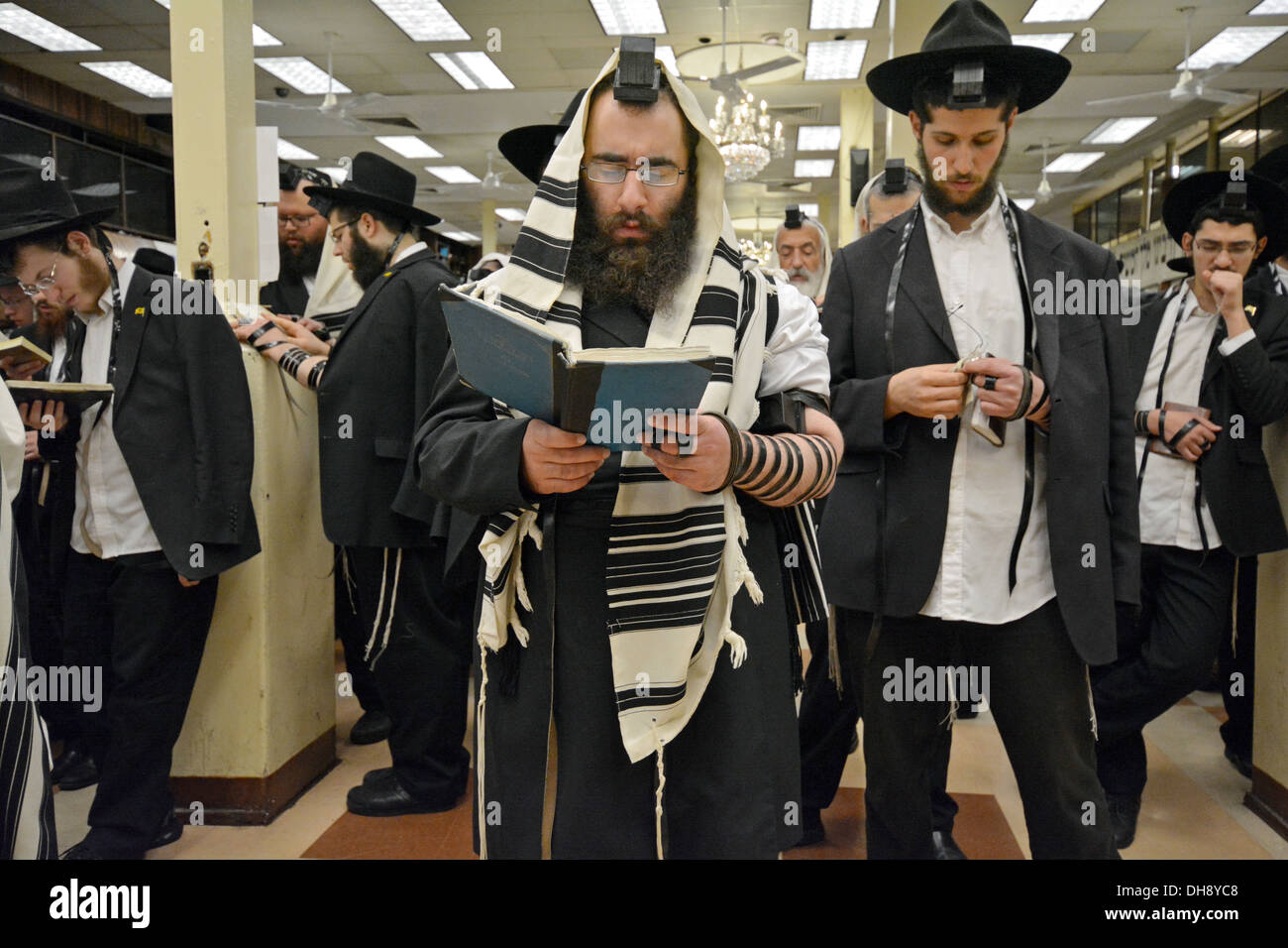 Group of religious Jews praying wearing Teffilin, phylacteries, and a prayer shawl at Lubavitch headquarters in Brooklyn, NY - Stock Image