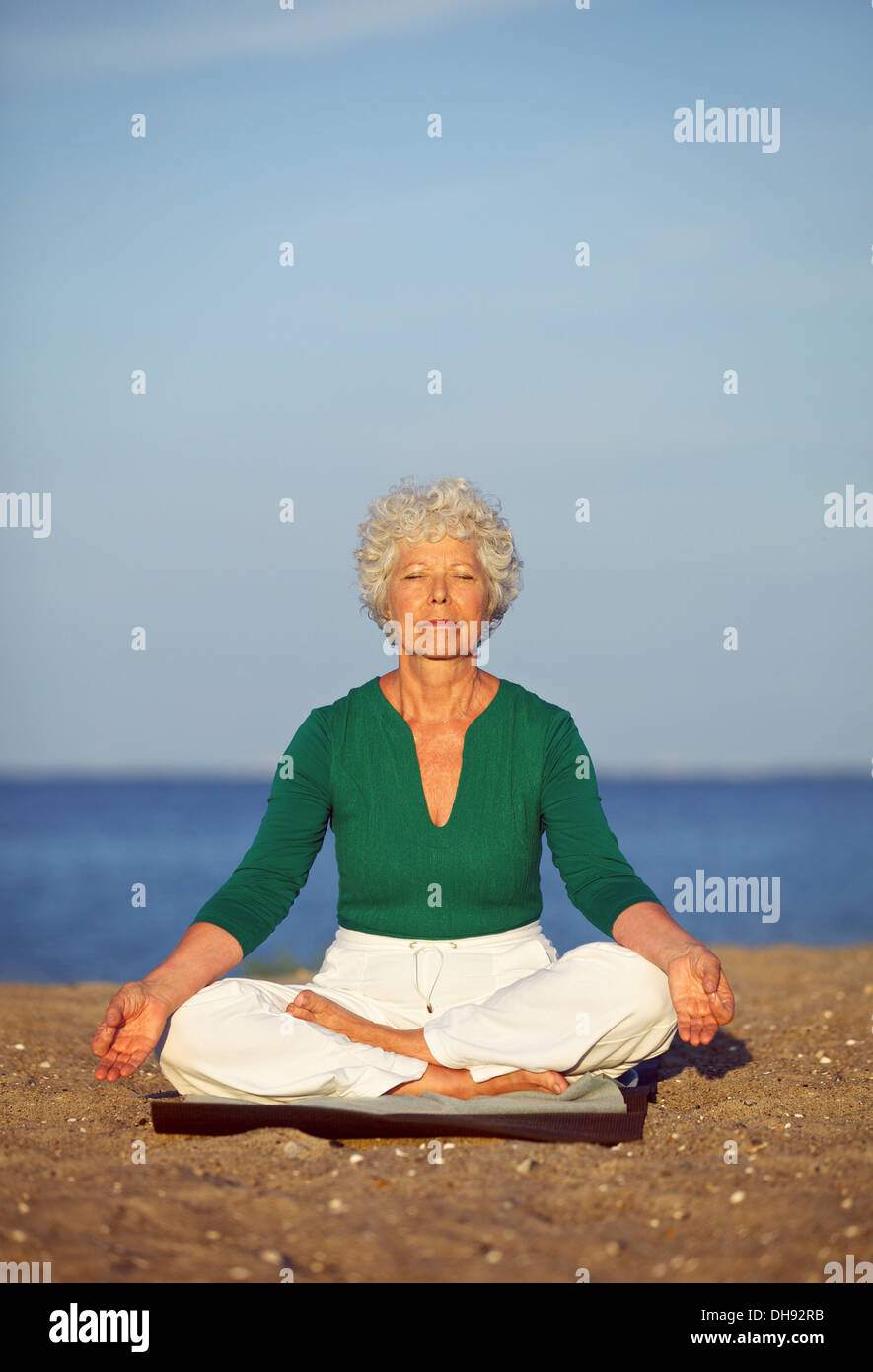 Portrait of the senior woman meditating on the seashore. Old woman relaxing by sea doing yoga. Meditation, yoga - Stock Image