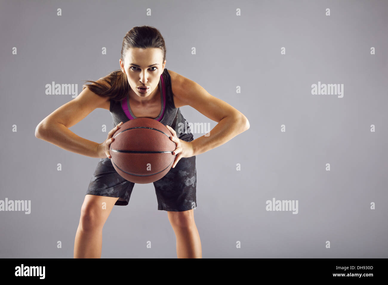 Portrait of young female basketball player passing the ball. Beautiful caucasian woman in sportswear playing basketball on grey - Stock Image