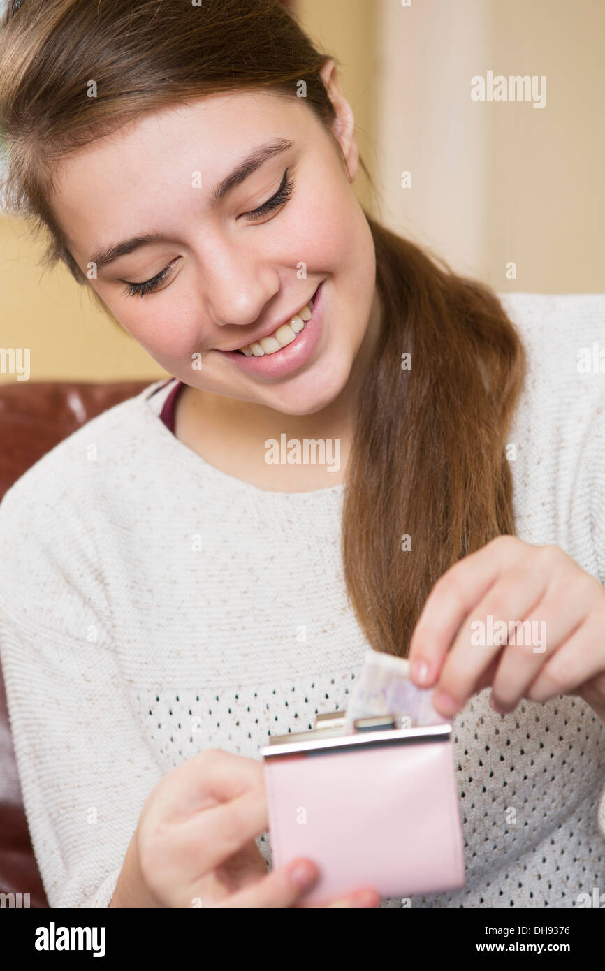 Happy Teenage Girl Putting Money In Purse - Stock Image