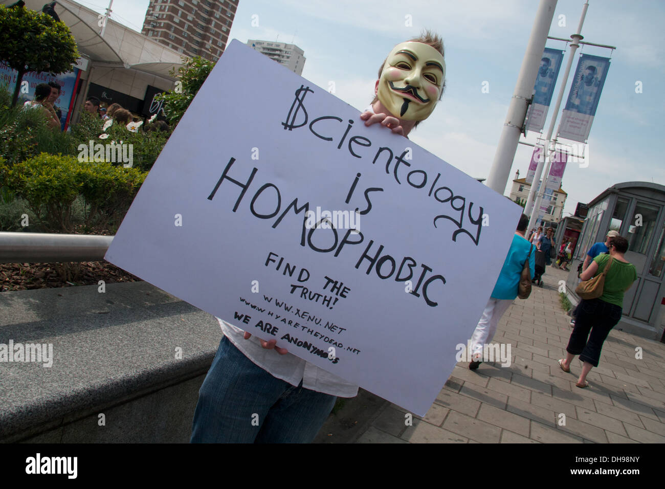 A protester wearing a Guy Fawkes V for Vendetta mask protests against Scientologists.  Scientology  is homophobic - Stock Image