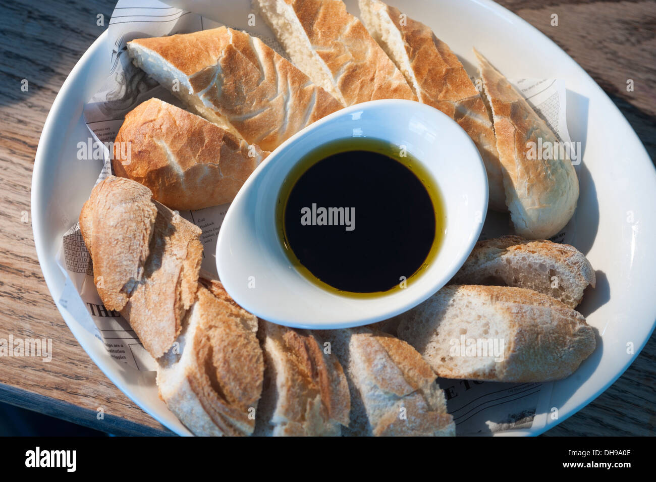 Bread served in a restaurant, with an olive oil and balsamic vinegar dip in the centre of the plate. - Stock Image