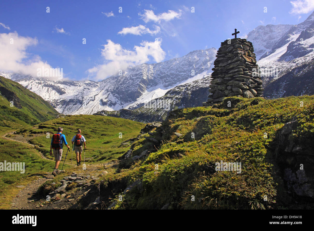 Two mountain walkers walking on path along cross on stone socle in the mountains of Pinzgau, Salzburgerland, Austria Stock Photo
