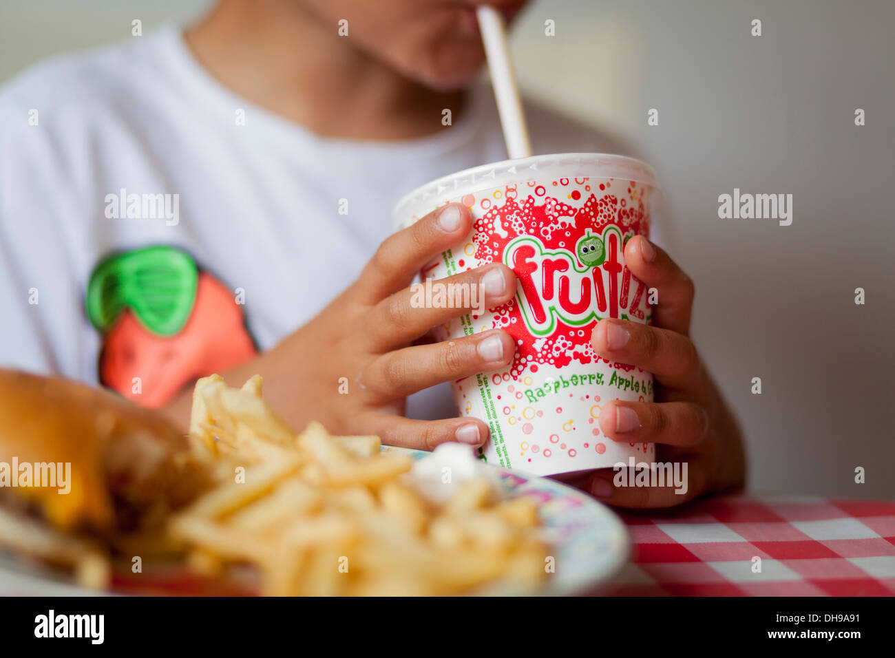Child drinking milkshake with a straw - Stock Image