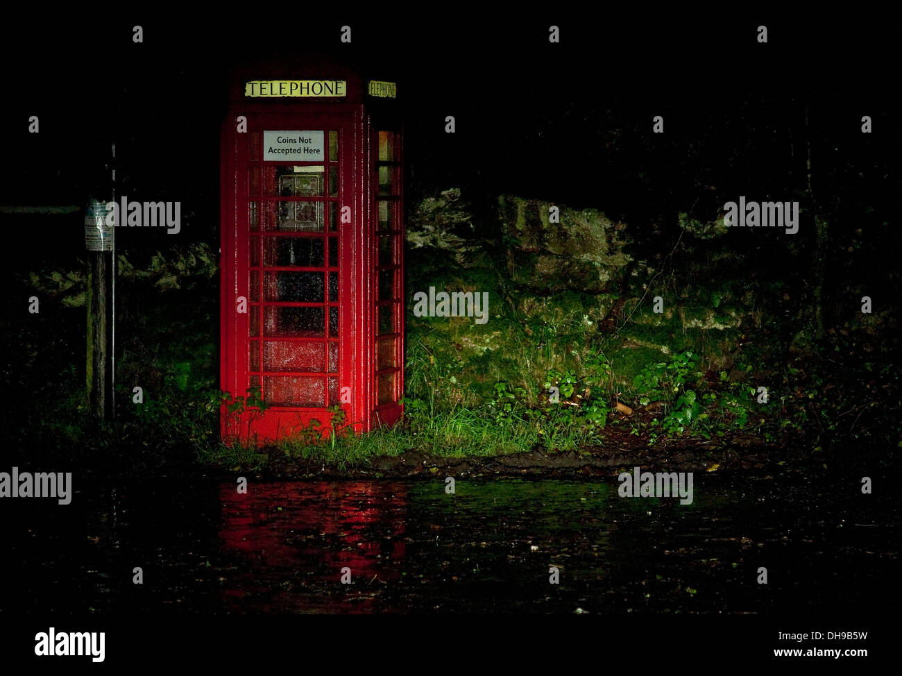 Red Telephone box seen in car headlights at night in the rain at Bradford Bodmin Moor - Stock Image