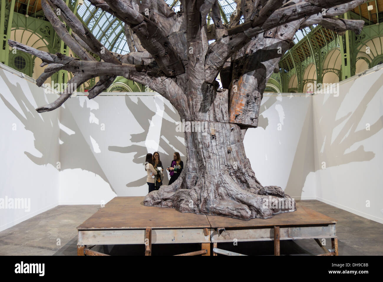 Young women visitor under the Iron Tree by Ai Weiwei at the Fiac 2013 (contemporary art fair) at le Grand Palais in Paris - Stock Image
