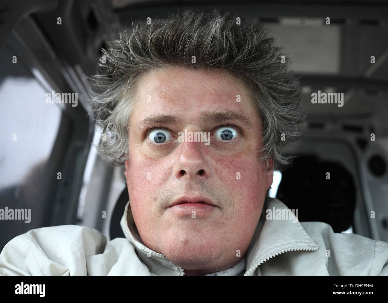 Wide eyed, odd expression on the face of a middle aged white male. - Stock Image