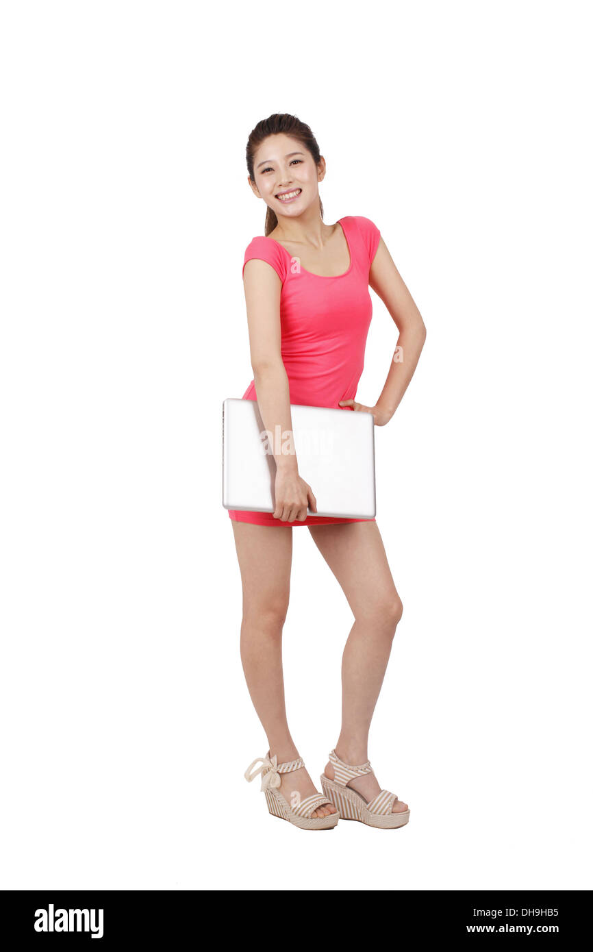 Young woman in pink dress holding laptop - Stock Image