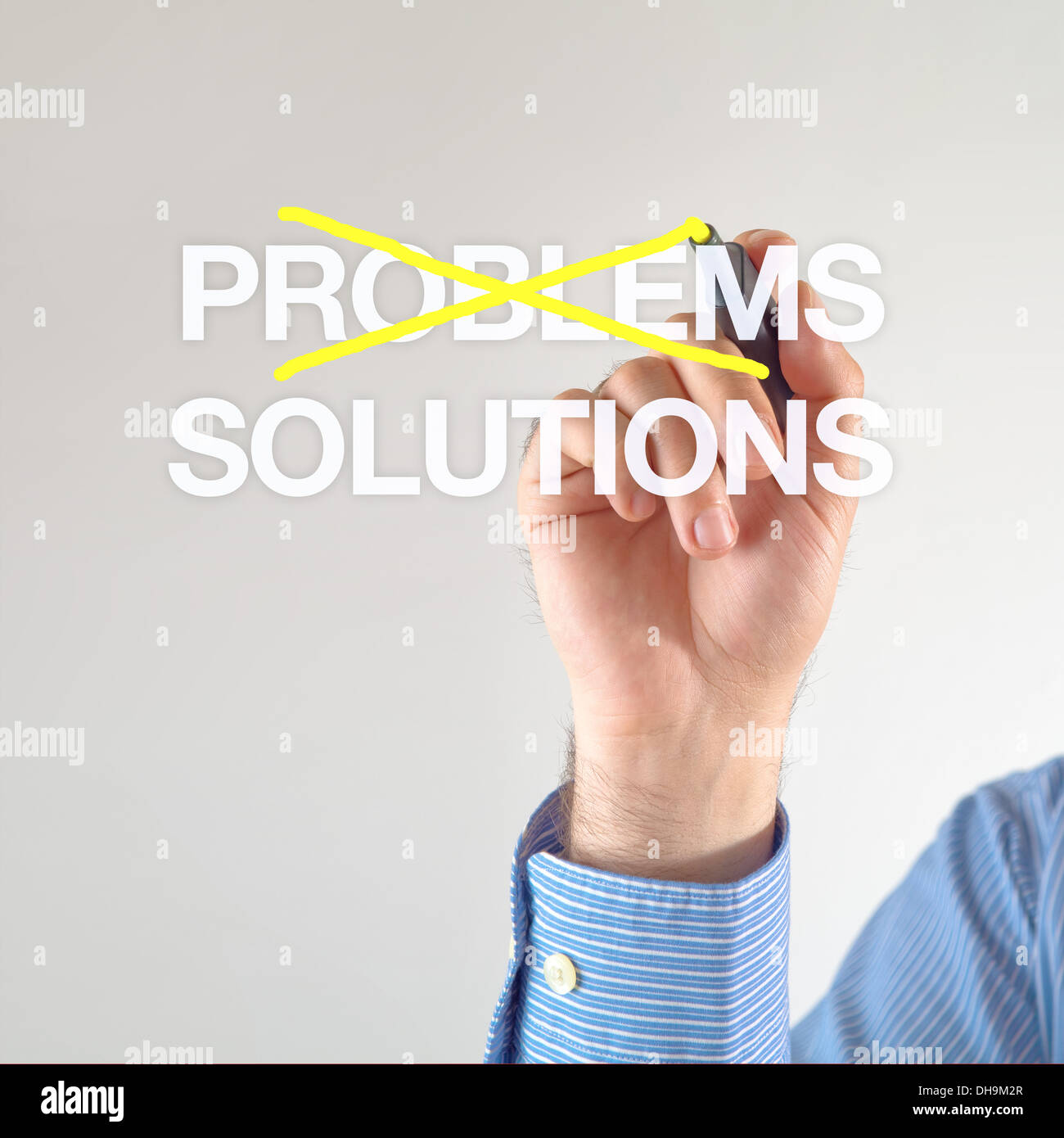 Solutions, not problems. Businessman crosses out problems for solutions with yellow marker pen on the screen - Stock Image
