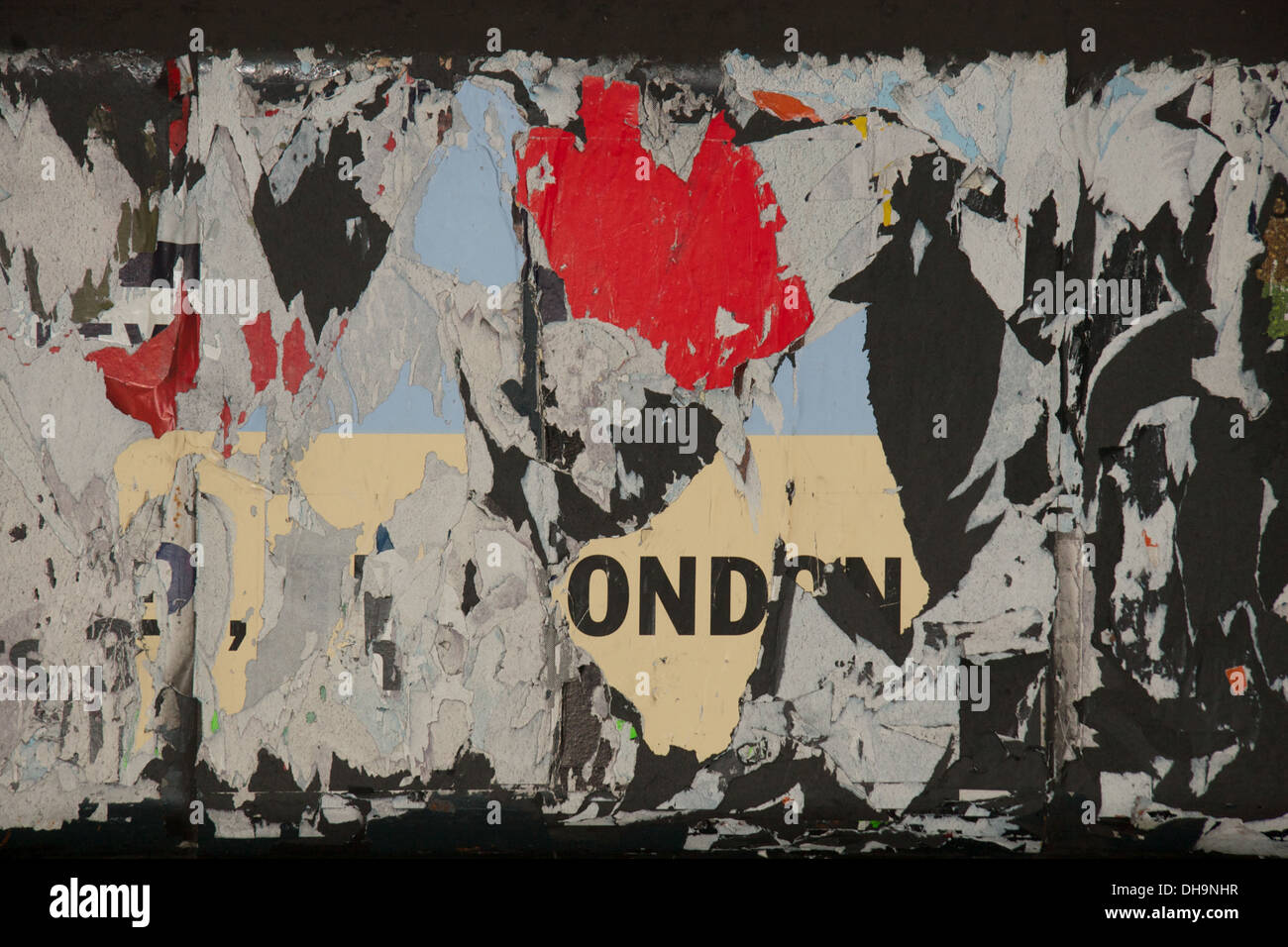Peeling layers of paper advertising posters on London underground - Stock Image