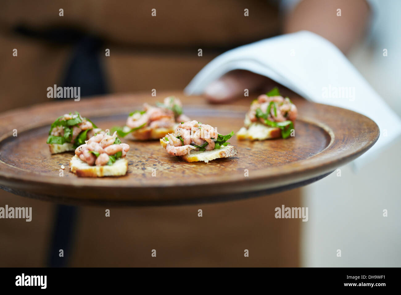 Close-up of a person serving canapés from a stylish wooden platter. - Stock Image