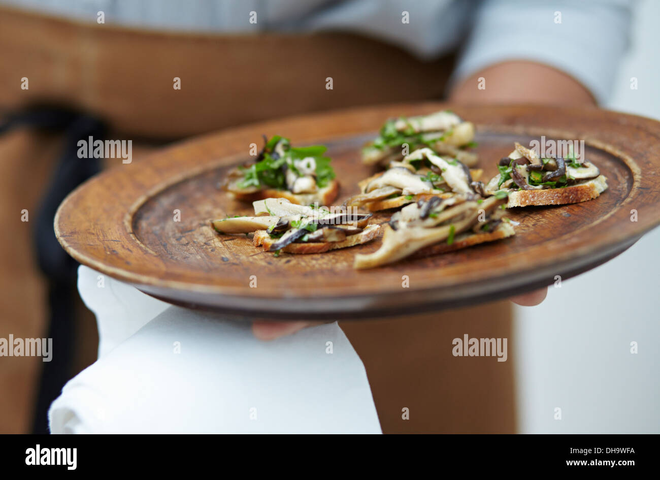 Close-up of a waitress holding a plate of canapés on a wooden platter. - Stock Image