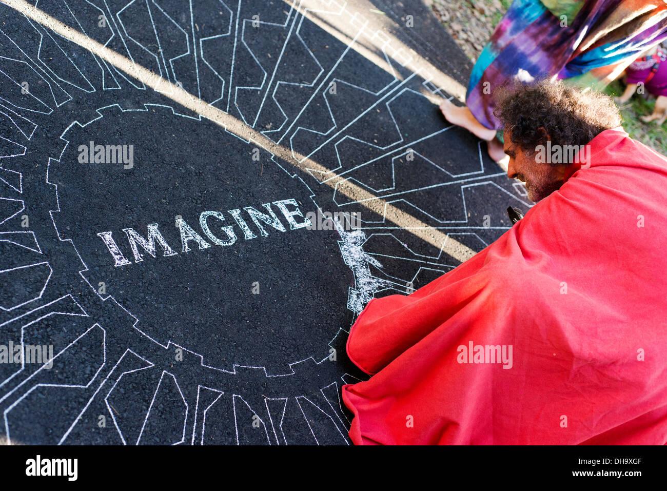 Man recreating the Central Park (NY) Imagine mural in Nimbin. - Stock Image