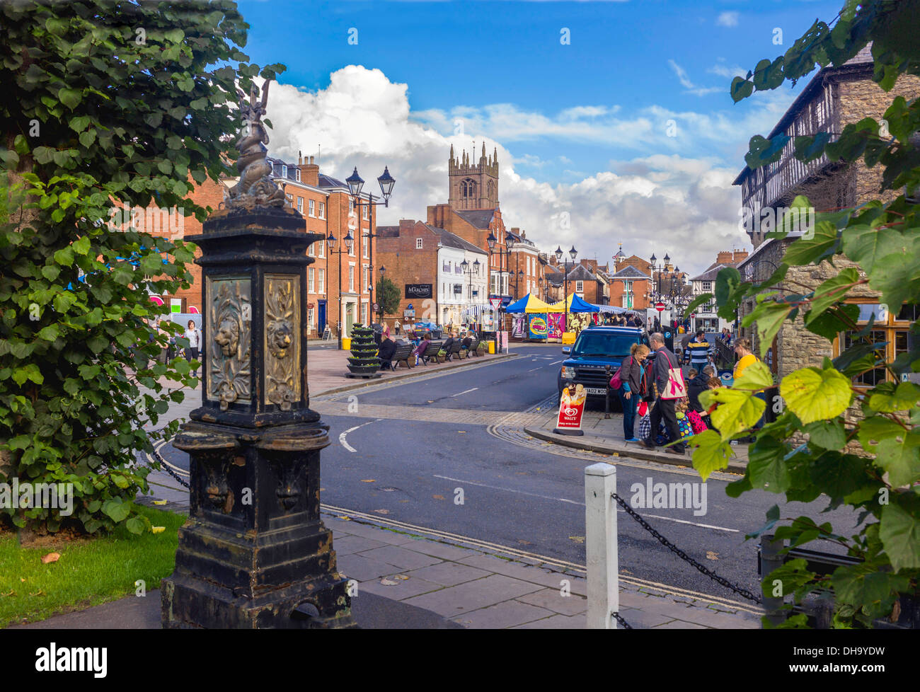 A view of Ludlow's 900 year old market with a ornamental disused water point framing the view across the colourful square - Stock Image