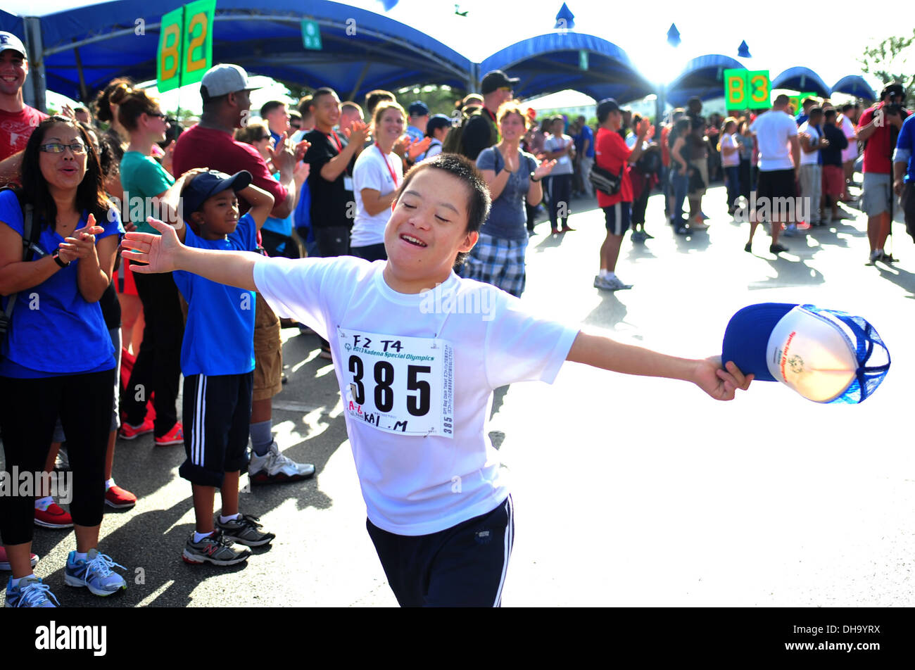Kai Minatogawa, 13 years old, runs down a row of cheerers during the Kadena Special Olympics on Kadena Air Base, Japan, Nov. 2, - Stock Image