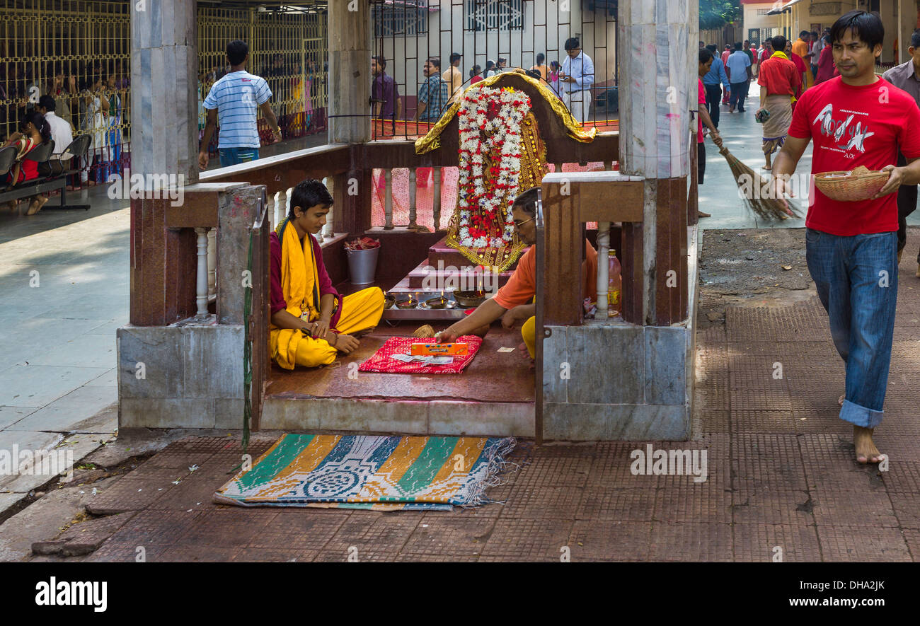 Hindu Brahman priests in the presence of a garlanded Hindu deity offer blessings to pilgrims at Kamakhya temple in Guwahati. - Stock Image