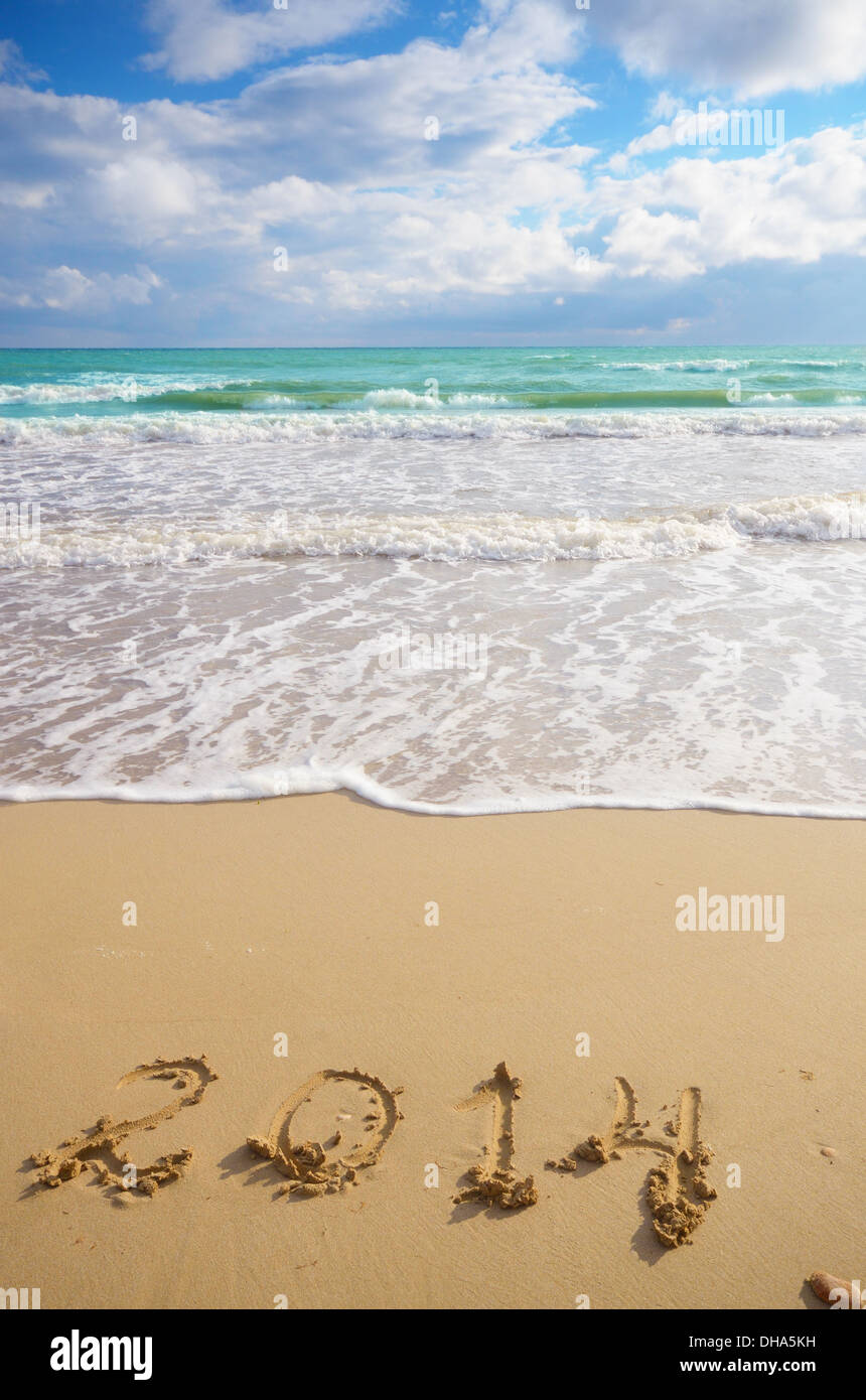 Year 2014 coming concept on beach sand, the wave is washing digits - Stock Image