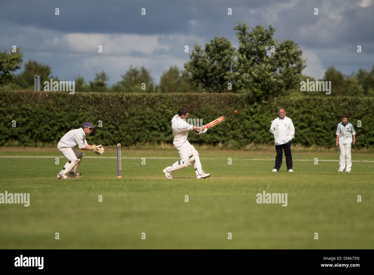 Village cricket. The batsman pulls the ball square of the wicket with the wicketkeeper waiting to pounce whilst a fielder and an - Stock Image