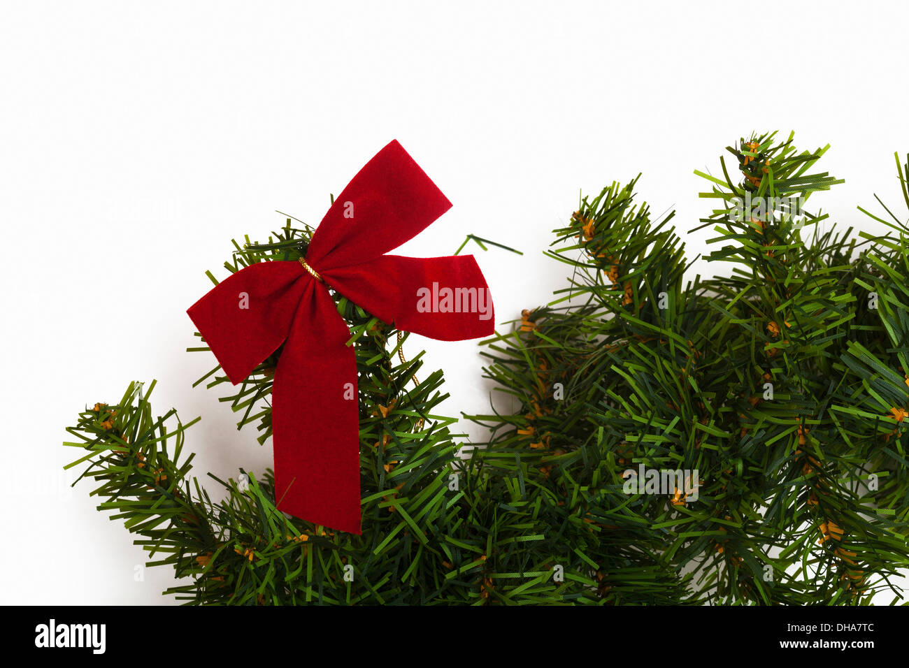 A red bow on a Christmas garland - Stock Image