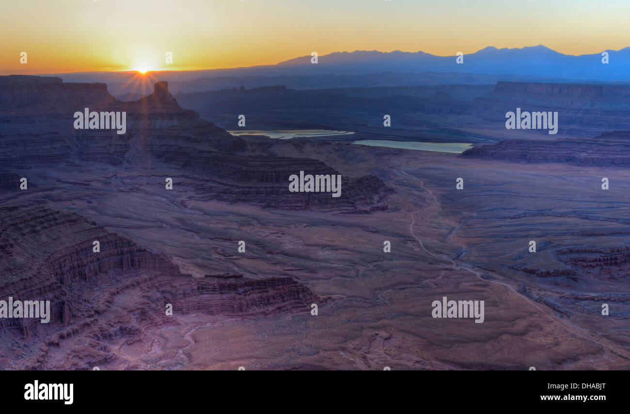 Spectacular sunrise over the purple mesas and and potash ponds seen from Overlook in Dead Horse Point State Park, Utah - Stock Image