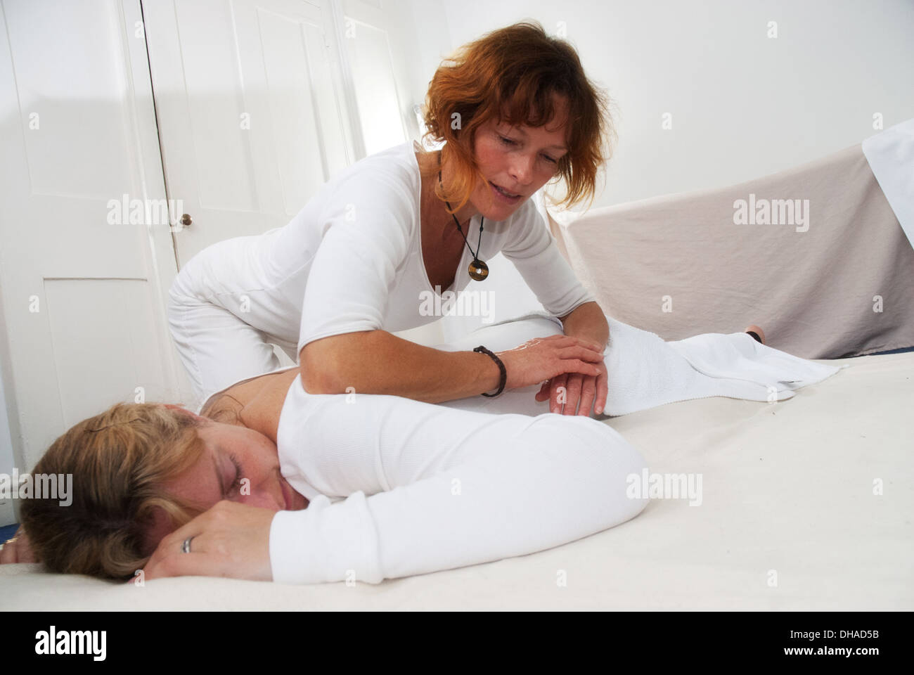 A masseur performing a shiatsu massage in a white treatment room - Stock Image
