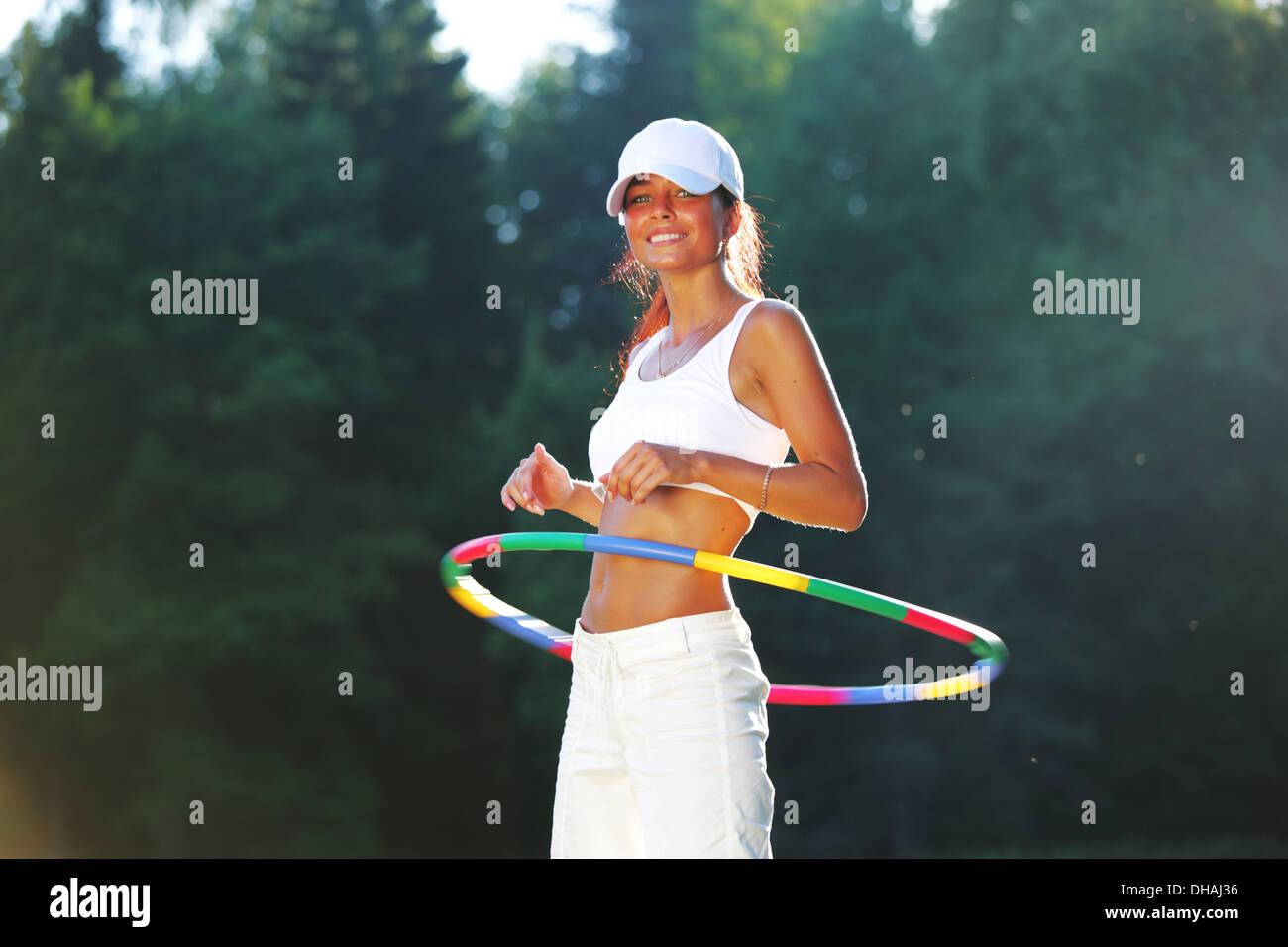 woman rotates hula hoop on nature background - Stock Image