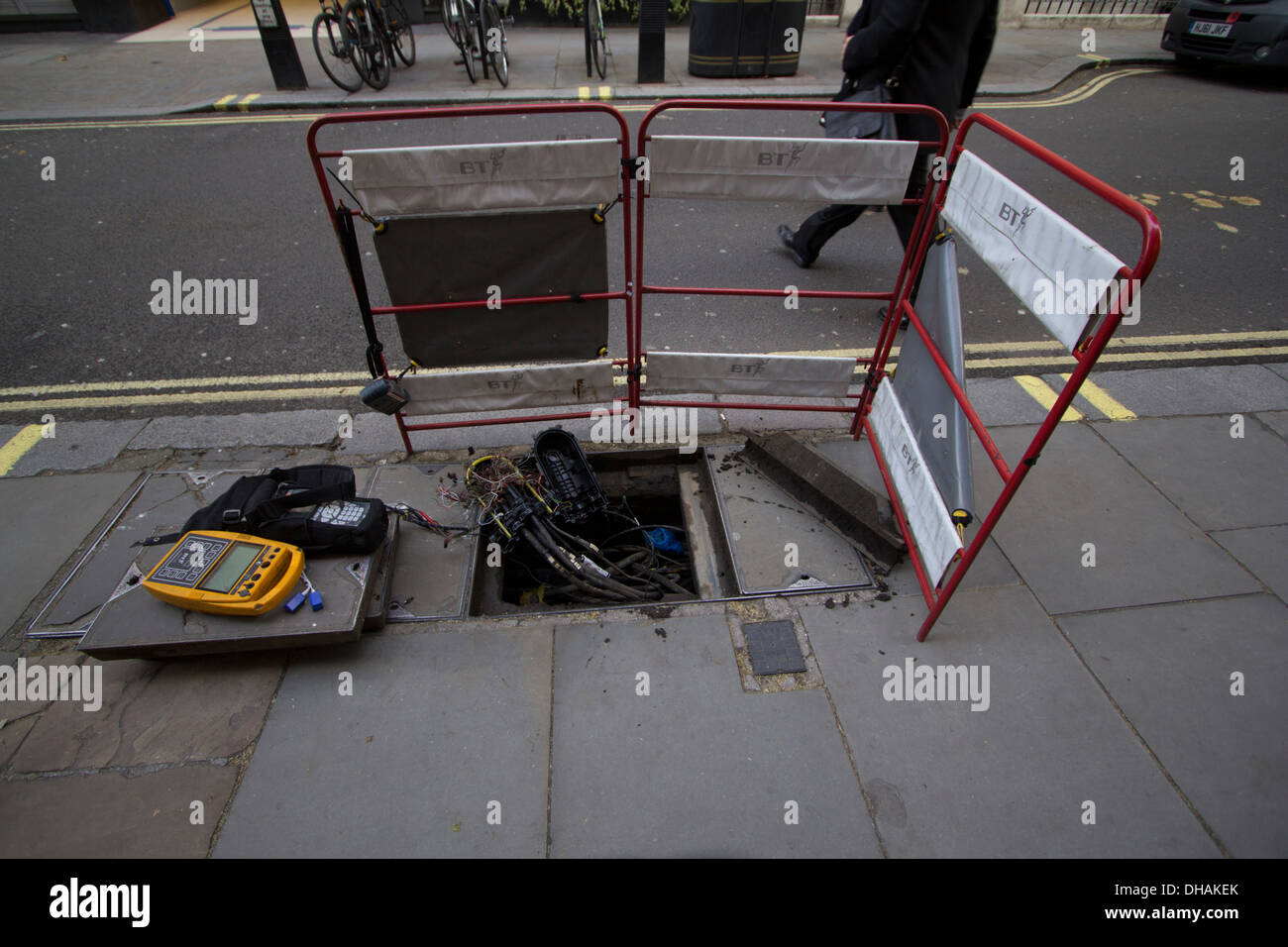 Hole in pavement, British telecom cables in London street, manhole awaiting repairs - Stock Image