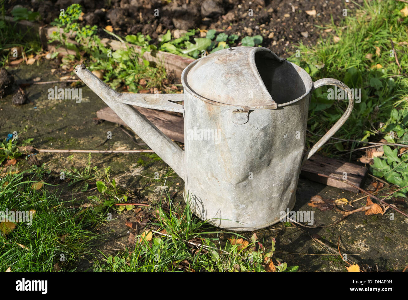 Old watering can on garden path - Stock Image