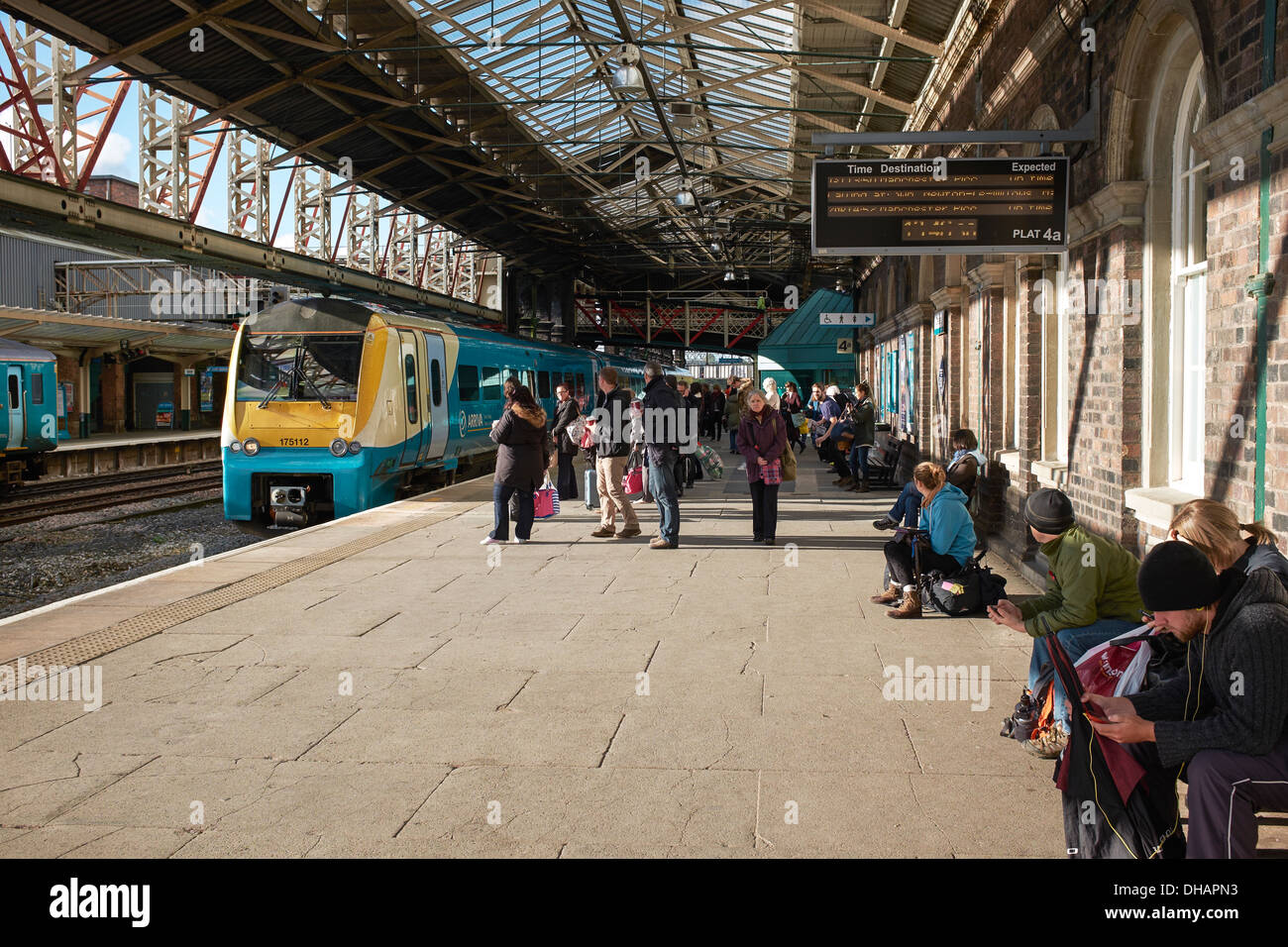Passengers on the platform at Chester Railway Station as an Arriva train approaches - Stock Image