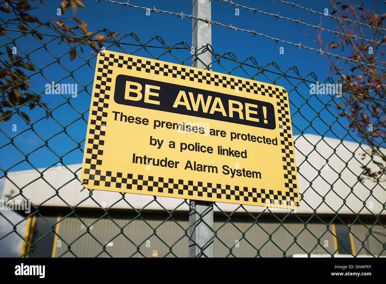 Security warning sign on the perimeter fence of an industrial unit - Stock Image
