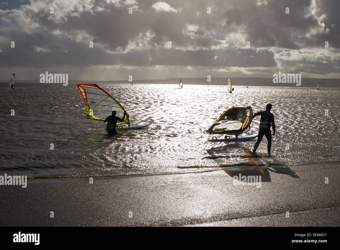 People windsurfing on the Marine Lake at West Kirby on the Wirral on a very cold blustery day - Stock Image