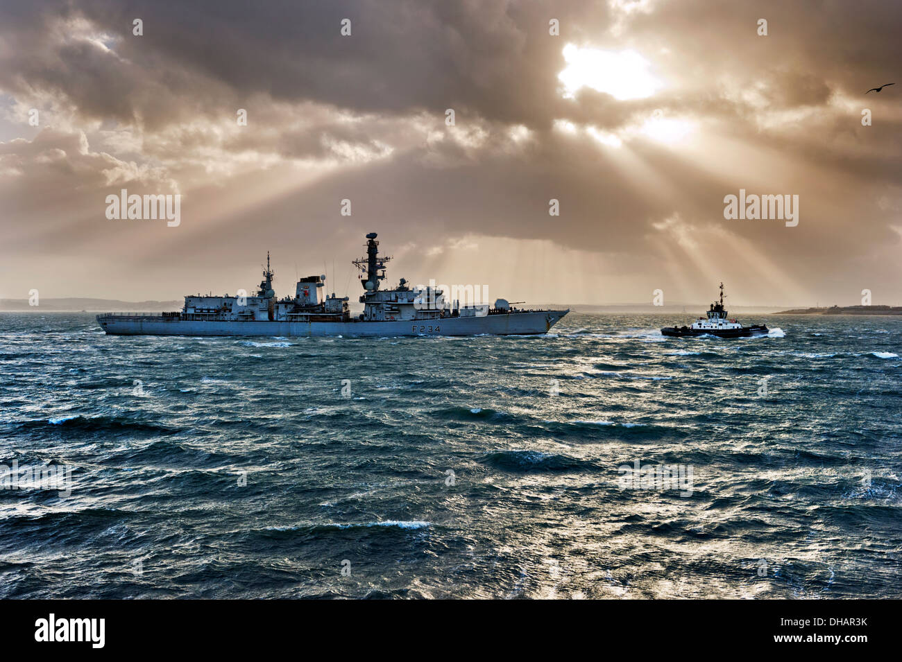 HMS Iron Duke, F234, of the Royal Navy being towed through The Solent by a tug into Portsmouth Harbour naval base, Hampshire, UK. - Stock Image