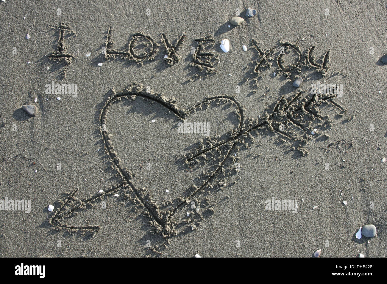 Love heart with arrow drawn in sand on the beach and the words 'I love you' - Stock Image