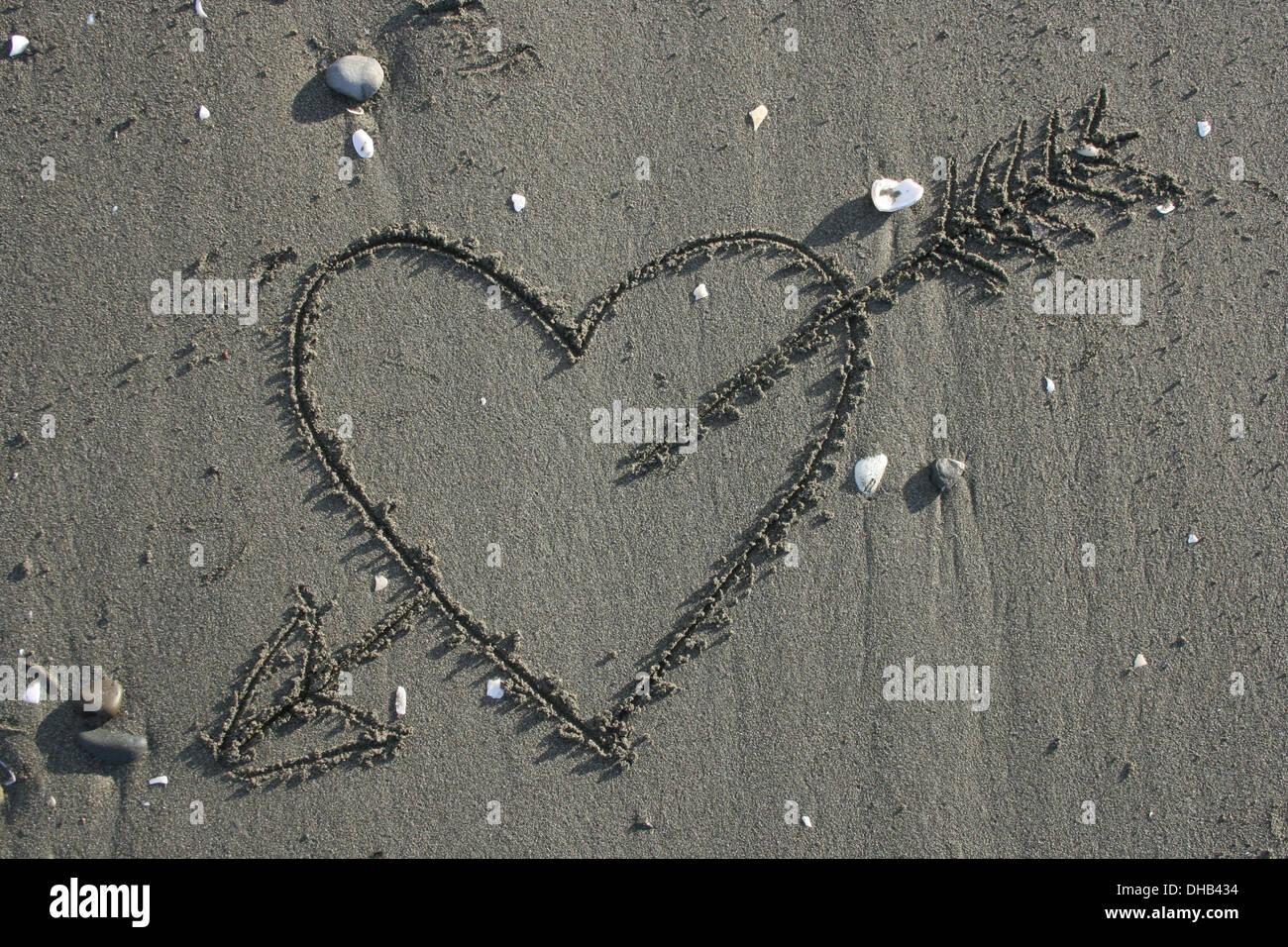 Love heart with arrow drawn in sand on the beach - Stock Image