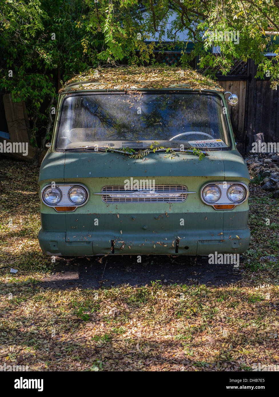 An old Chevrolet van sits, ignored, in a driveway in Ojai, California almost completely covered with autumn leaves. - Stock Image