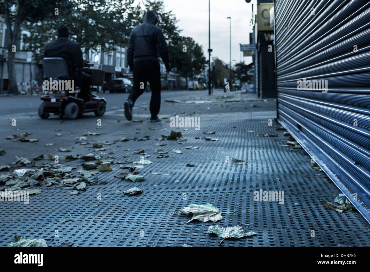 A youth passes a man on a mobility scooter along the Caledonian Road in Islington, North London, on a morning in - Stock Image