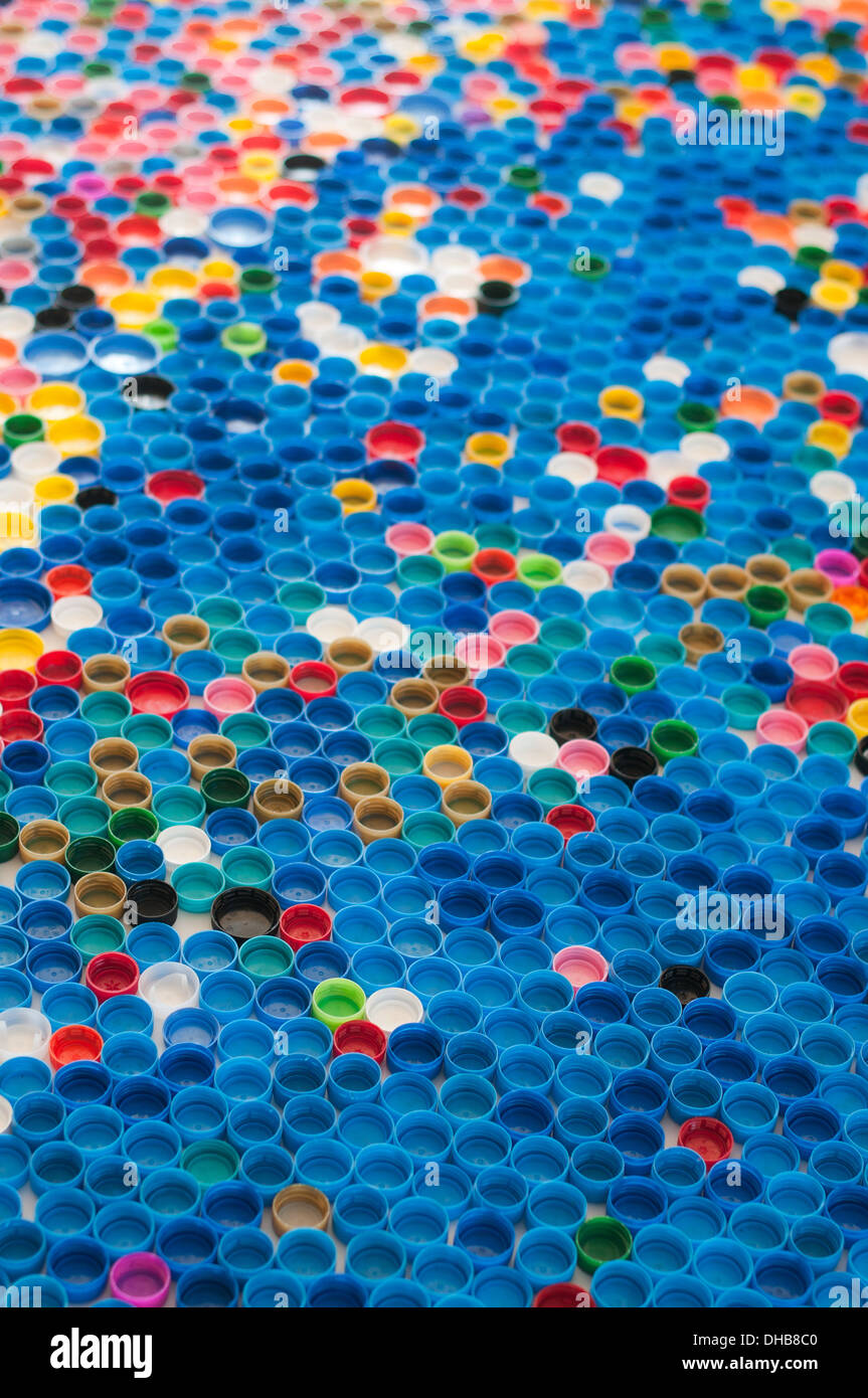 Colorful plastic bottle caps in a row - Stock Image