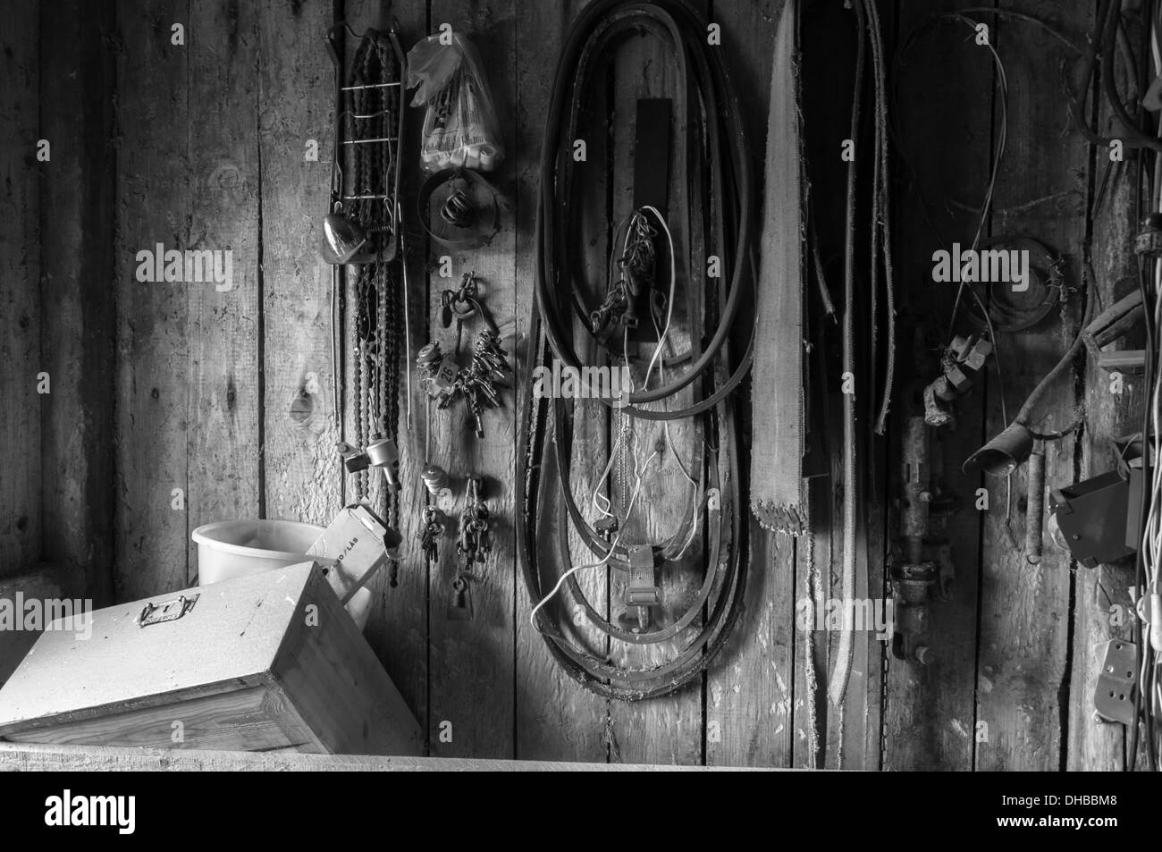 Tools and belts on an abandoned workshop wall - Stock Image