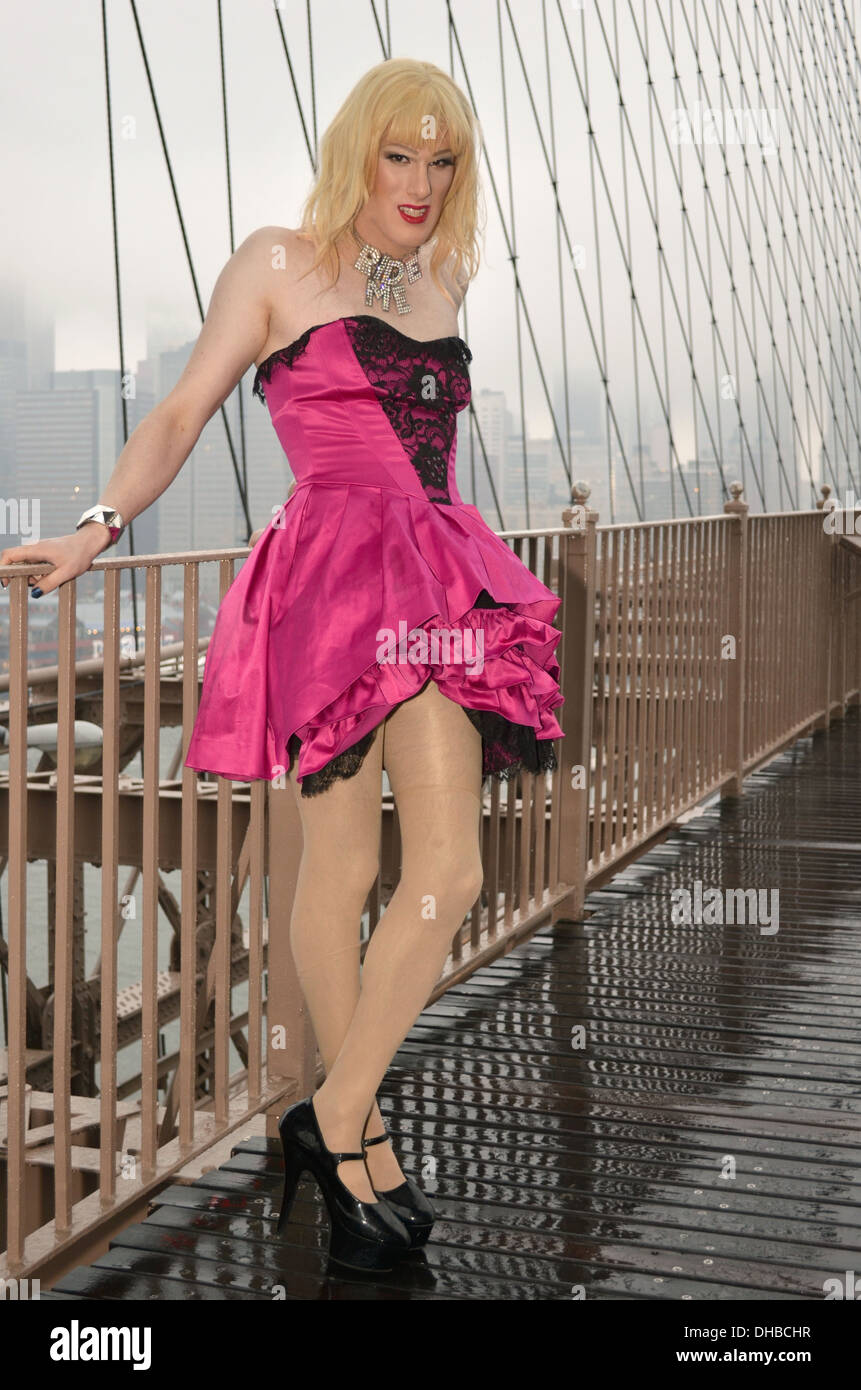 A man in a dress photographed in the rain on the Brooklyn Bridge in New York City Stock Photo