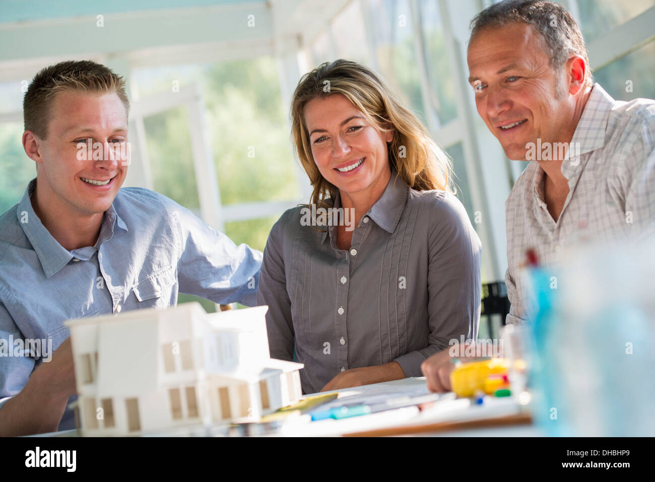 A farmhouse kitchen. A model of a house on the table. Planning and designing a house build. Three people. - Stock Image