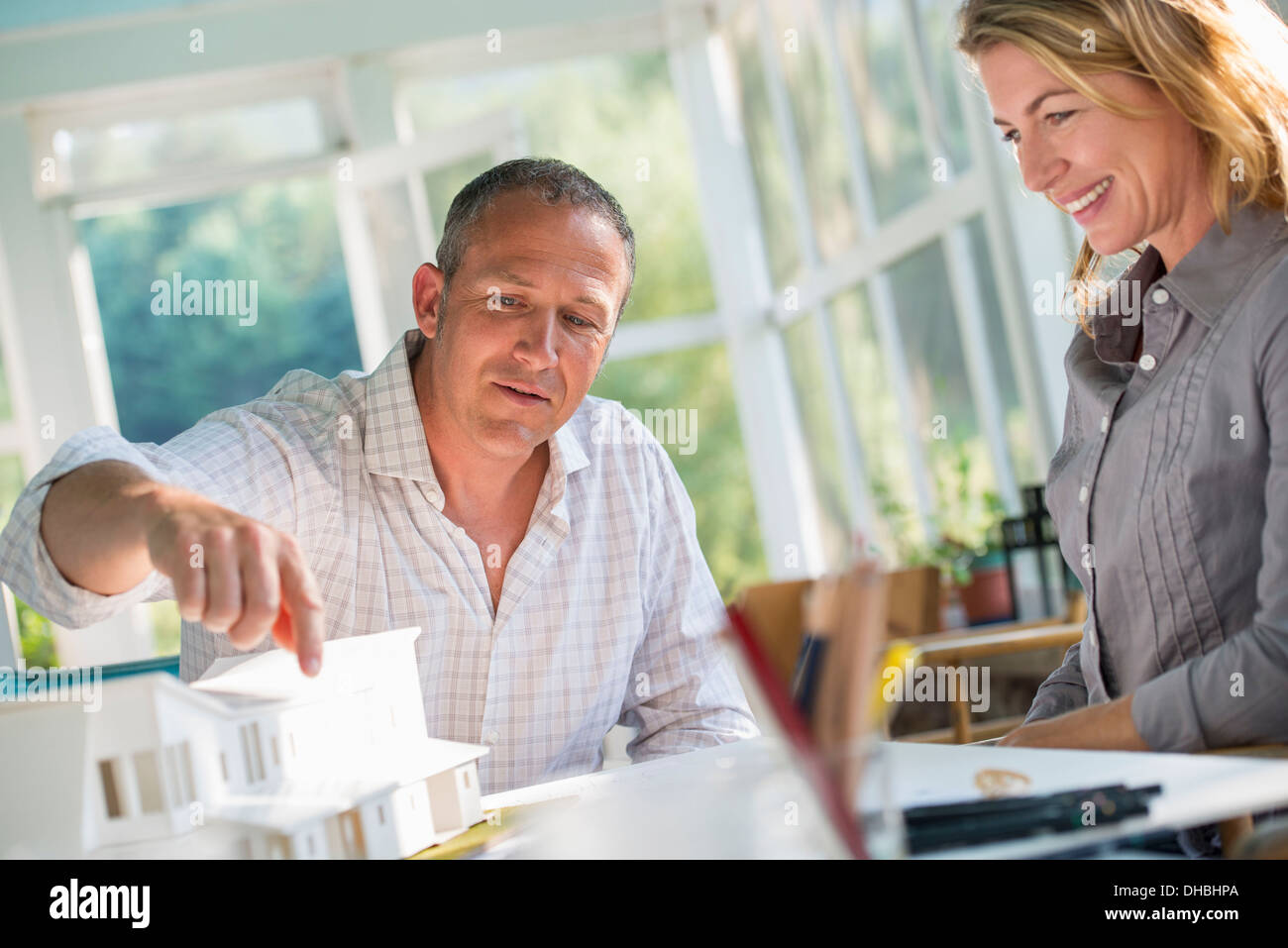 A farmhouse kitchen. A model of a house on the table. Designing a house. A couple. - Stock Image