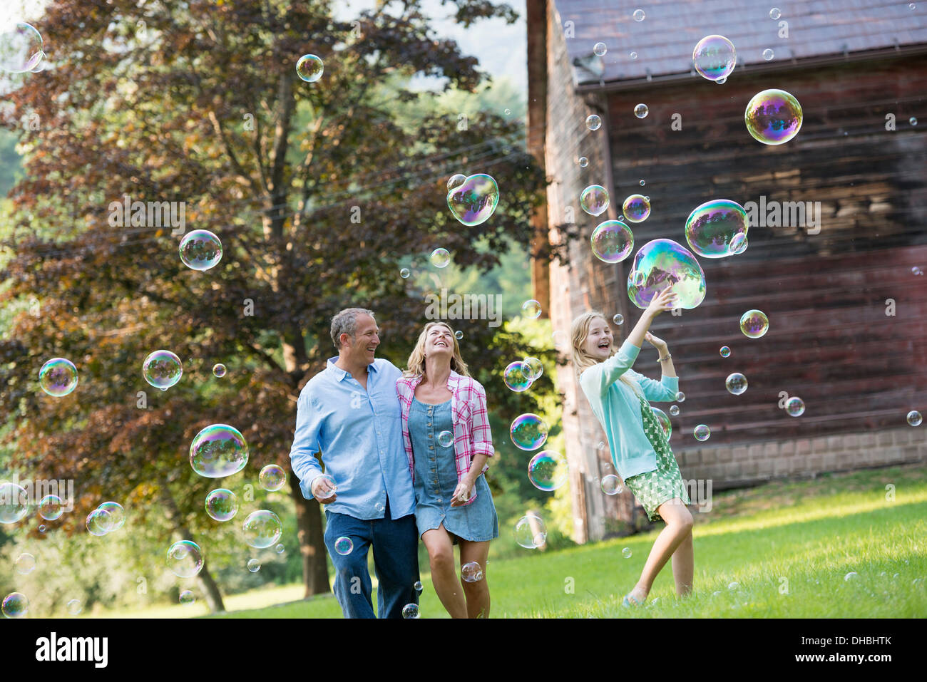 A family sitting on the grass outside a bar, blowing bubbles and laughing. - Stock Image