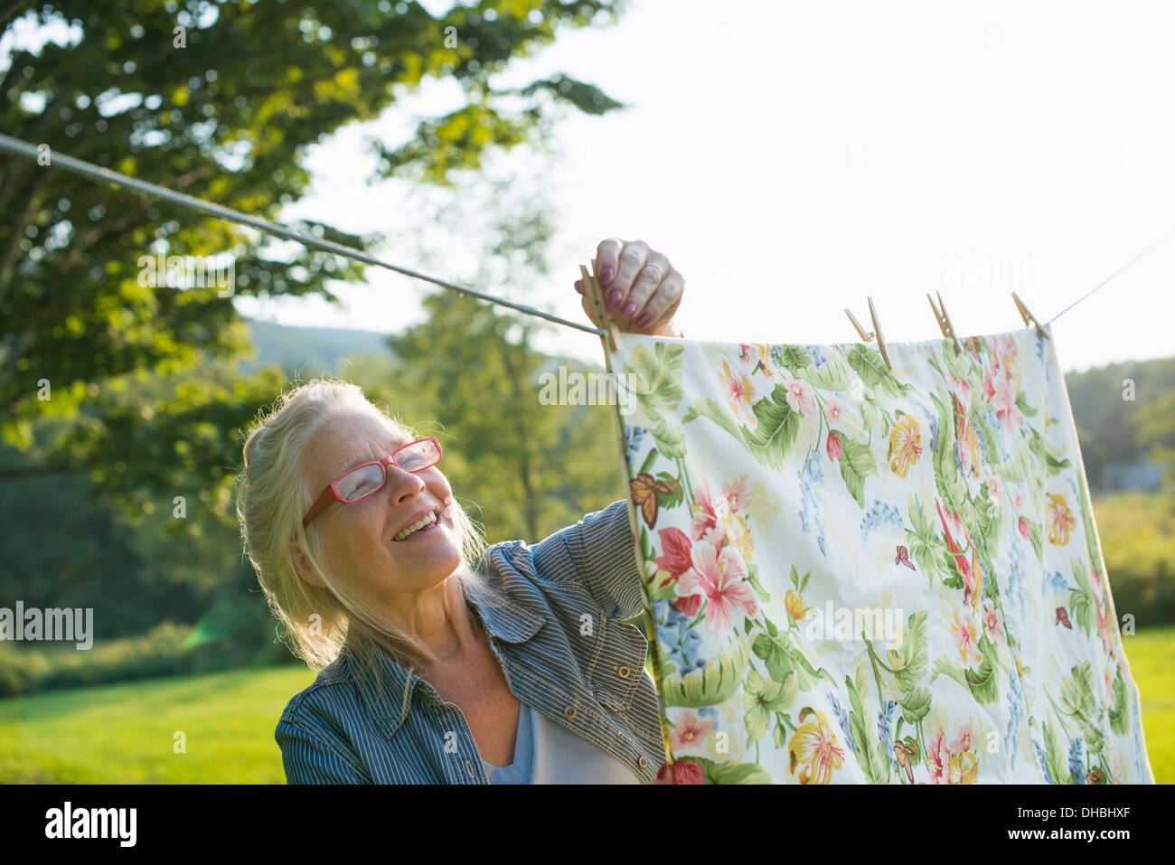 A woman hanging laundry on the washing line, in the fresh air. - Stock Image