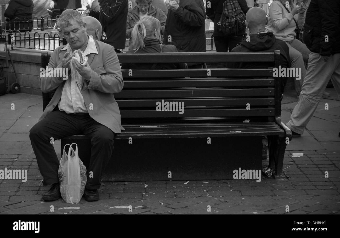 Man sitting on bench preparing to eat hot dog - Stock Image