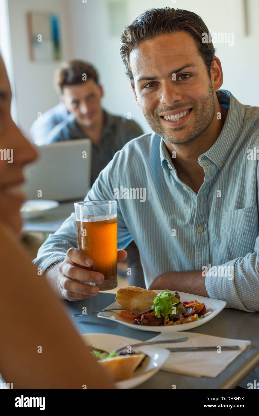 A group of men and women in a cafe, eating and drinking and enjoying each other's company. - Stock Image