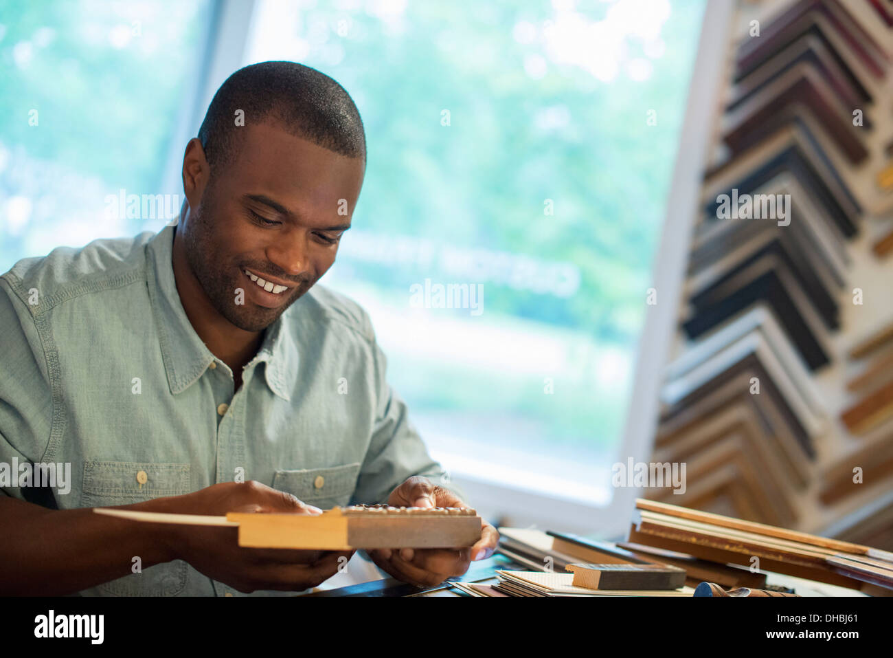 A young man at his workbench in a picture framing studio. Surrounded by samples. - Stock Image