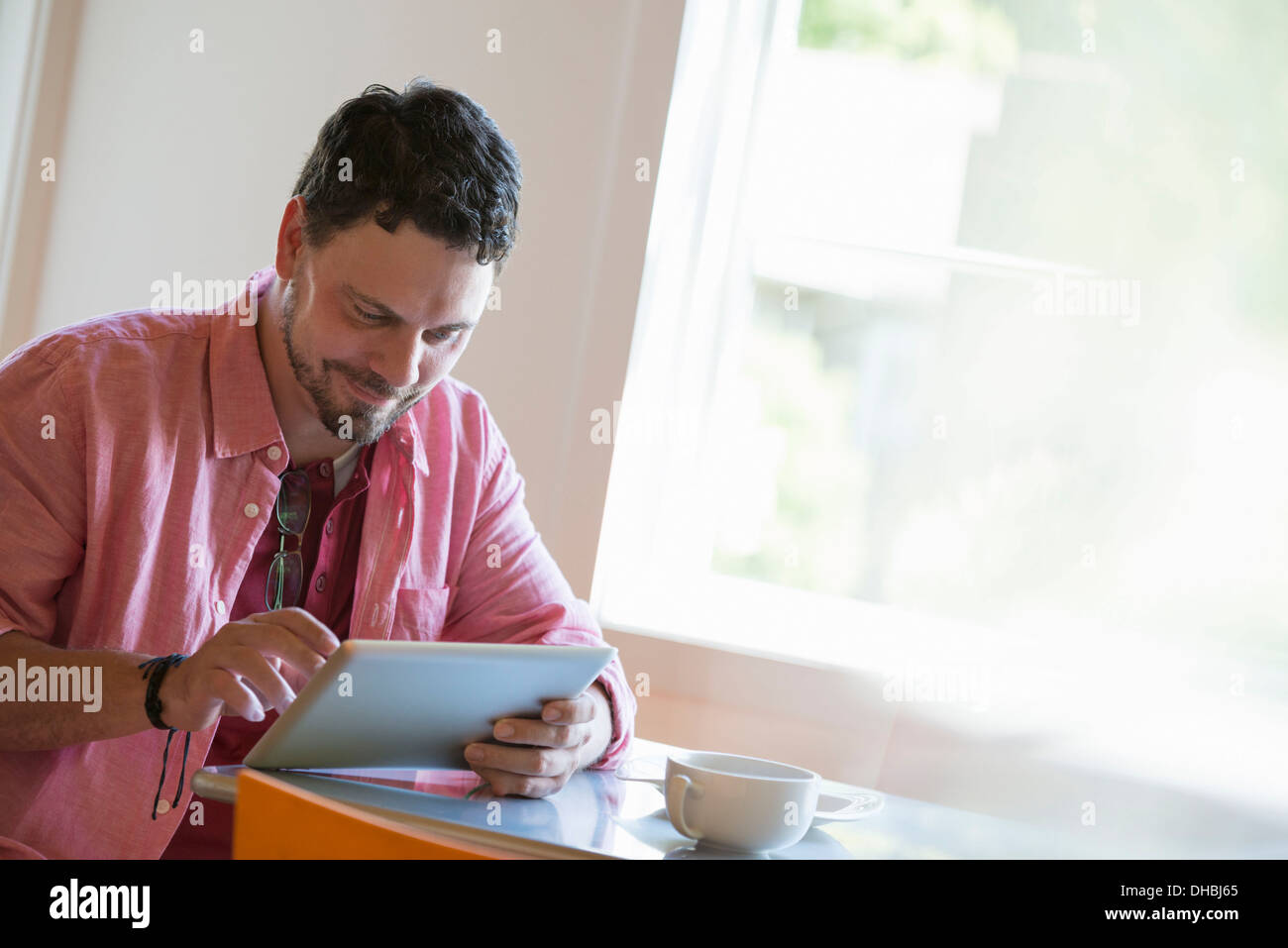 A man sitting at a cafe table, using a digital tablet. - Stock Image