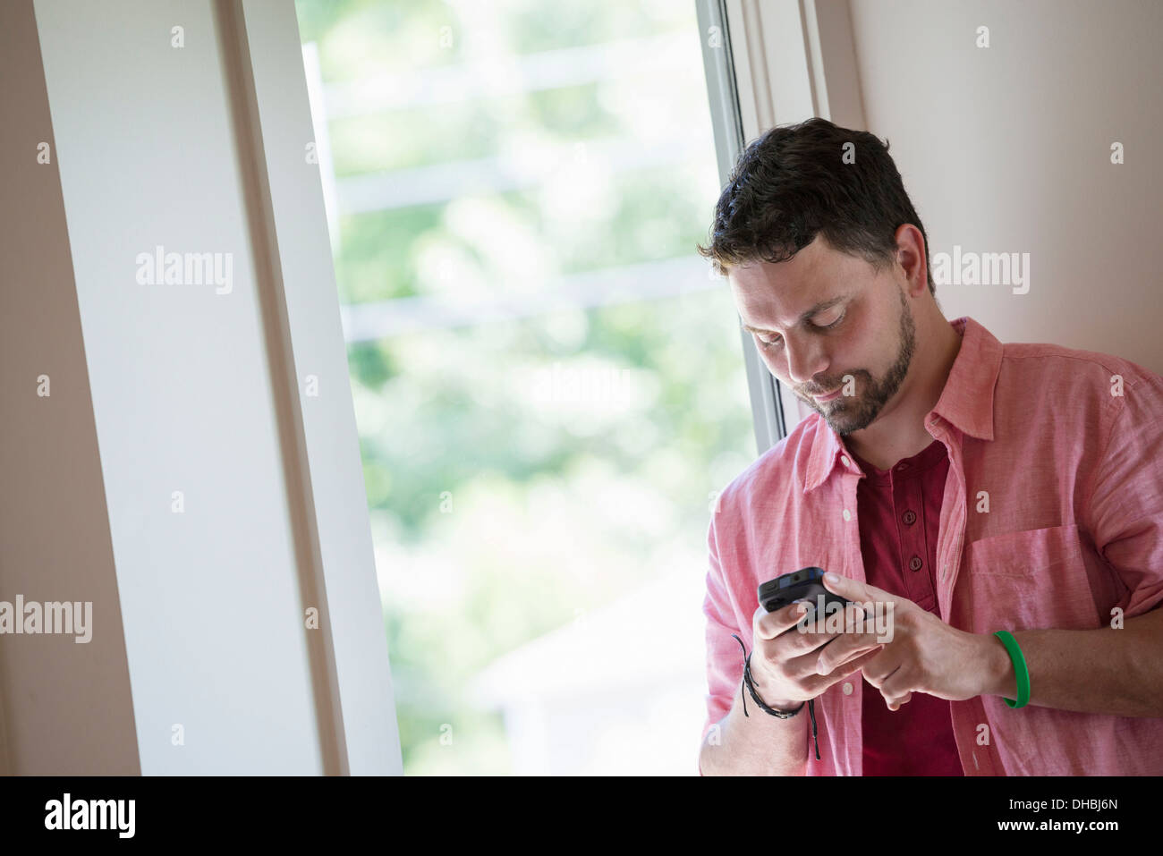 A man standing in a quiet corner of a cafe, using a smart phone. - Stock Image