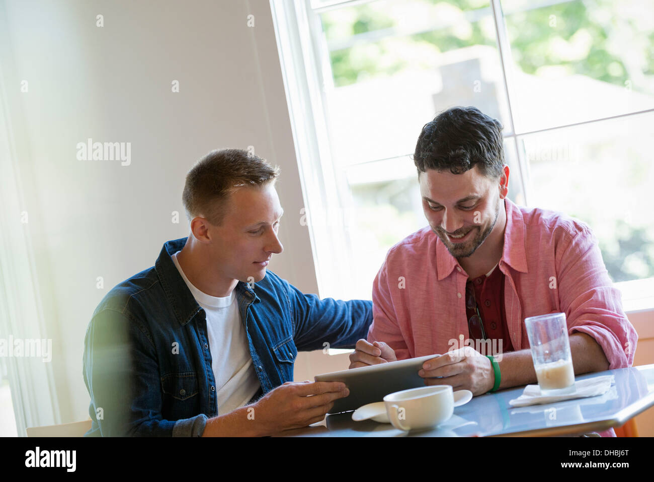 Two men at a cafe table, using a digital tablet. - Stock Image