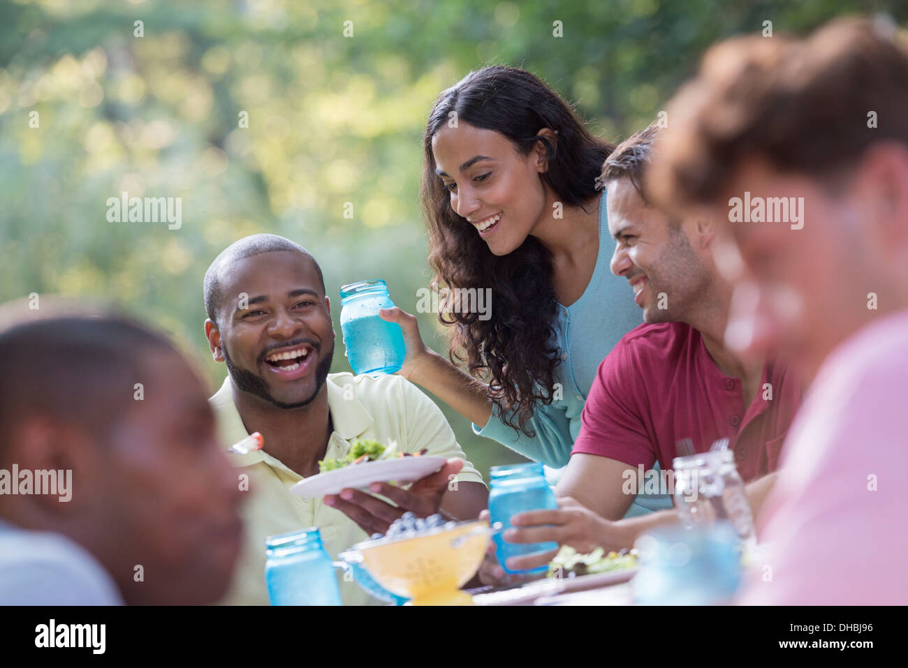 A group of people having a meal outdoors, a picnic. Men and women. - Stock Image
